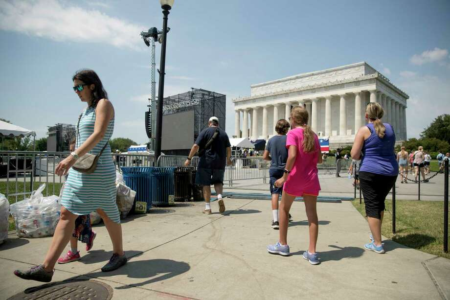 "Visitors to the National Mall walk near the Lincoln Memorial as workers set up for President Donald Trump's 'Salute to America' event honoring service branches on Independence Day, Tuesday, July 2, 2019, in Washington. President Donald Trump is promising military tanks along with ""Incredible Flyovers & biggest ever Fireworks!"" for the Fourth of July. Photo: Andrew Harnik, AP / Copyright 2019 The Associated Press. All rights reserved"