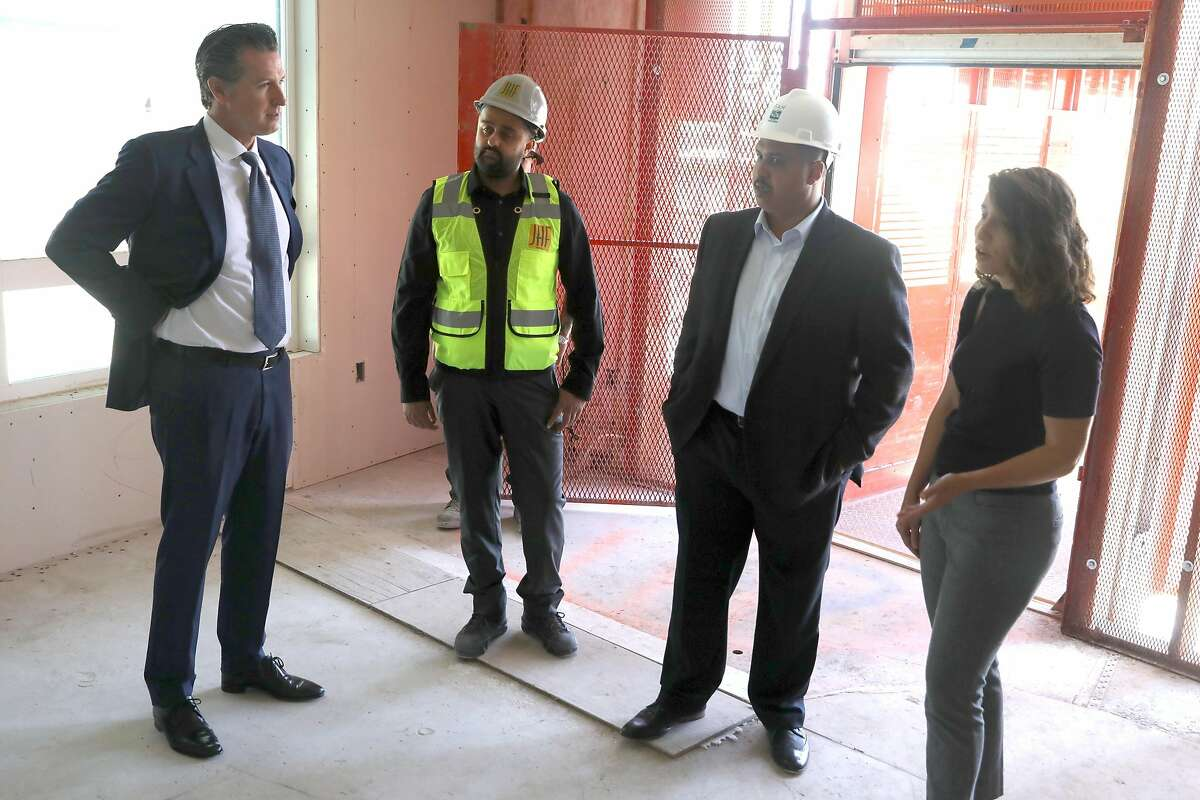Above: Gov. Gavin Newsom (left); project manager Kyan Hakimi; Welton Jordan, builder EAH Housing's head of real estate development and Emeryville Mayor Ally Medina in an apartment. Left: Newsom and Hakimi.
