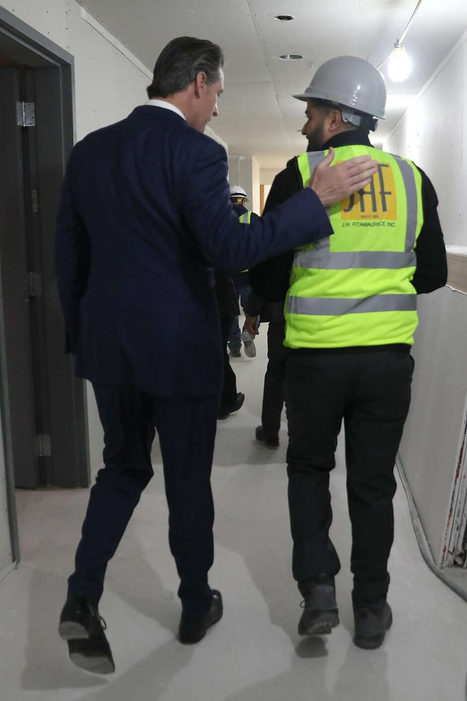 Governor Gavin Newsom takes a walk with JHF project manager Kyan Hakimi as they take a look at Estrella Vista Apartments, a new affordable housing development under construction on Tuesday, July 2, 2019, in Emeryville, Calif.