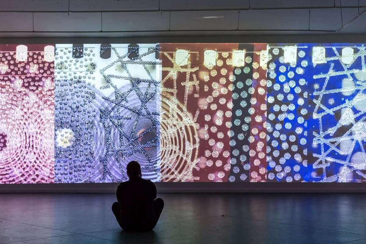 A visitor watches Sabine Gruffat's analog-digital projection