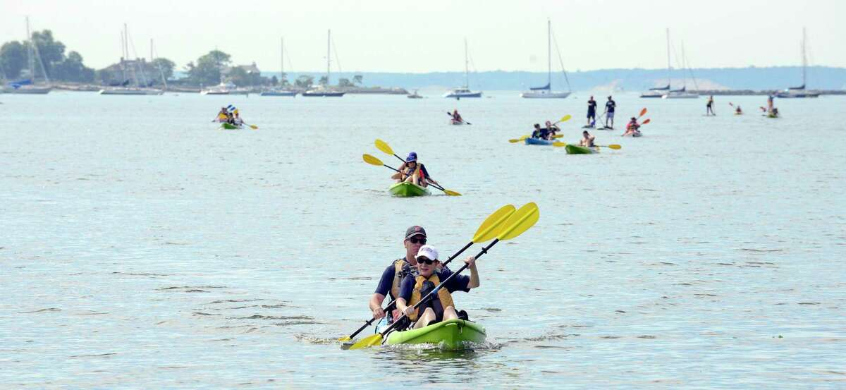 Participants paddle into shore during the second annual SoundWaters Flotilla from Cove Island Park to Boccuzzi Park on July 14, 2018 in Stamford, Connecticut.