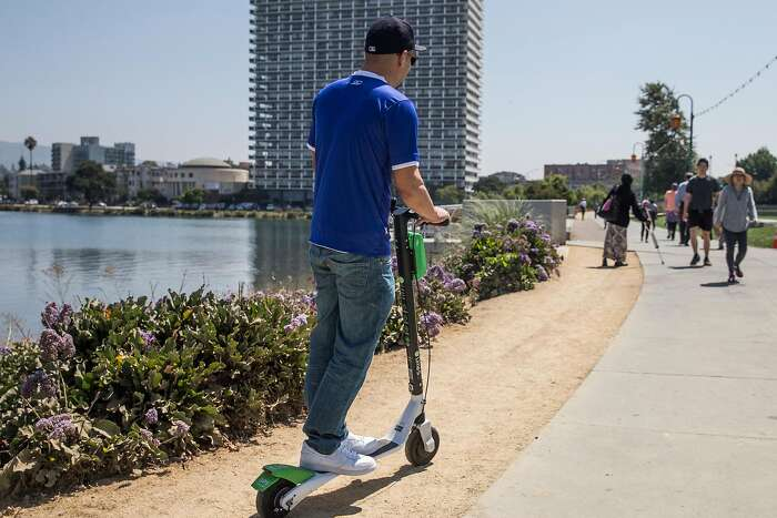 A man zooms past pedestrians while riding a Lime electronic scooter around Lake Merritt in Oakland, Calif. Thursday, Aug. 16, 2018.