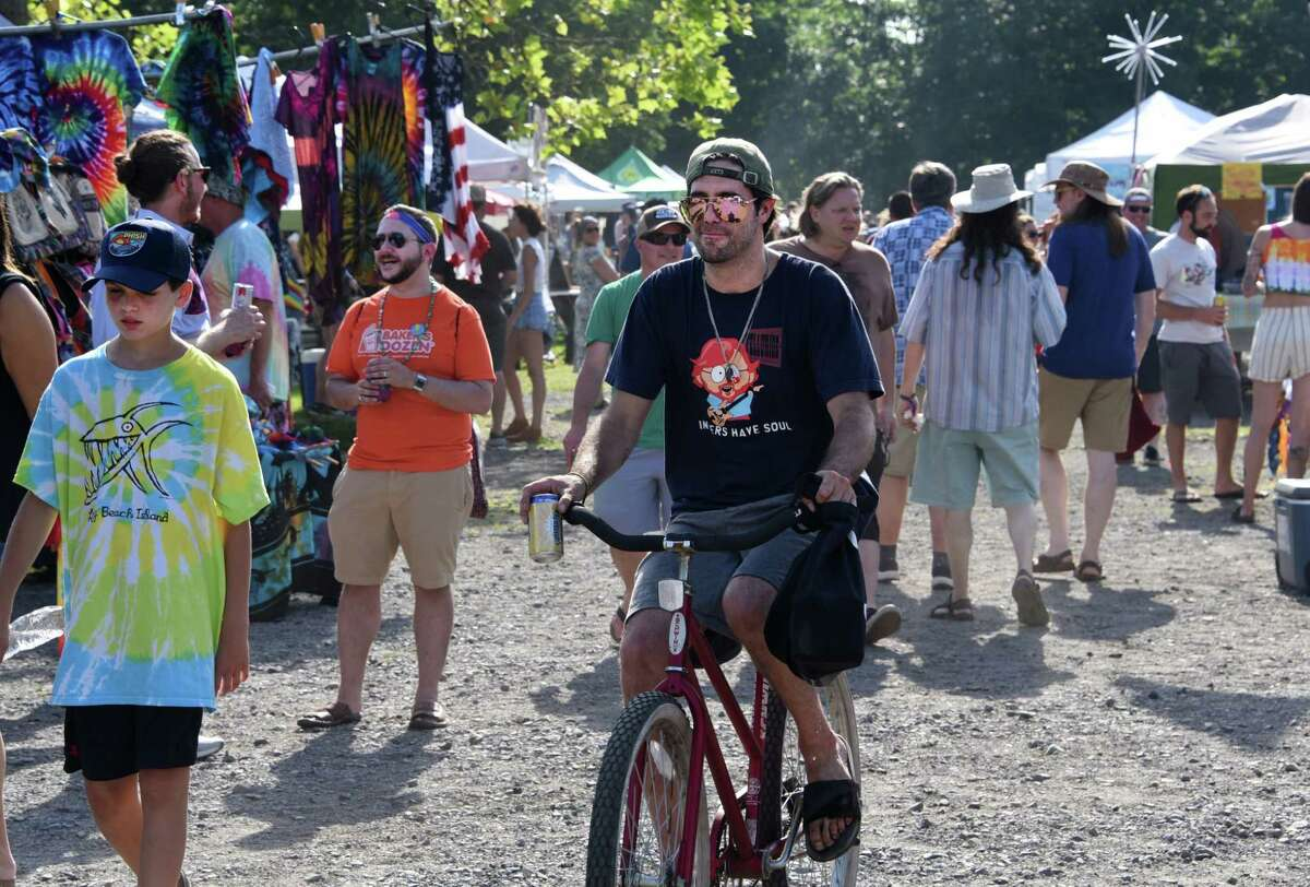 People walk and bike through Shakedown Street a couple hours before Phish performs at the Saratoga Performing Arts Center on Tuesday, July 2, 2019 in Saratoga Springs, N.Y. This is the first show of a two-day stop. (Lori Van Buren/Times Union)