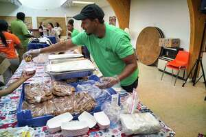 Corry McDonald, volunteer and site supervisor and Keiajah Washington, background, with the Schenectady County Summer Youth Program, serve families food during a SiCM free lunch program at the Greater Faith Christian Center on Tuesday, July 2, 2019, in Schenectady, N.Y. The Schenectady Community Ministries (SiCM), has begun their 25th year of serving summer meals for children. The program feeds children breakfast and lunch at various fixed and mobile sites through August 30th. SiCM is an organization made up of 52 congregations that served 53,150 meals last summer. The locations of the breakfast or lunch sites can be found at  www.sicm.us .   (Paul Buckowski/Times Union)