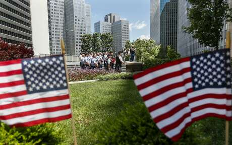 Pittsburgh firefighters watch a ceremony of the changing of an American flag during a Flag Day celebration, Friday, June 14, 2019, in downtown Pittsburgh. (AP Photo/Keith Srakocic)