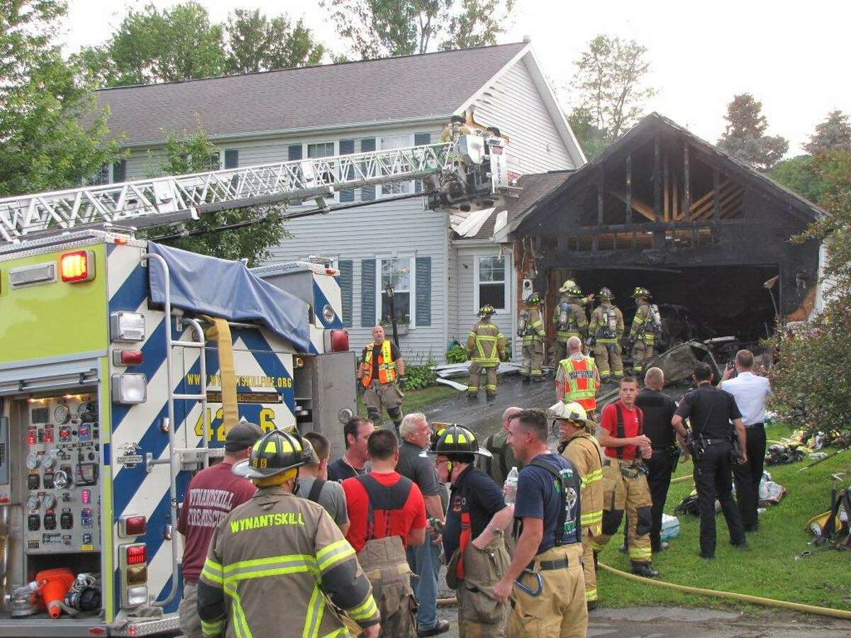 An attached garage was heavily damaged by smoke and flames on Tuesday evening in North Greenbush. (Marty Miller)