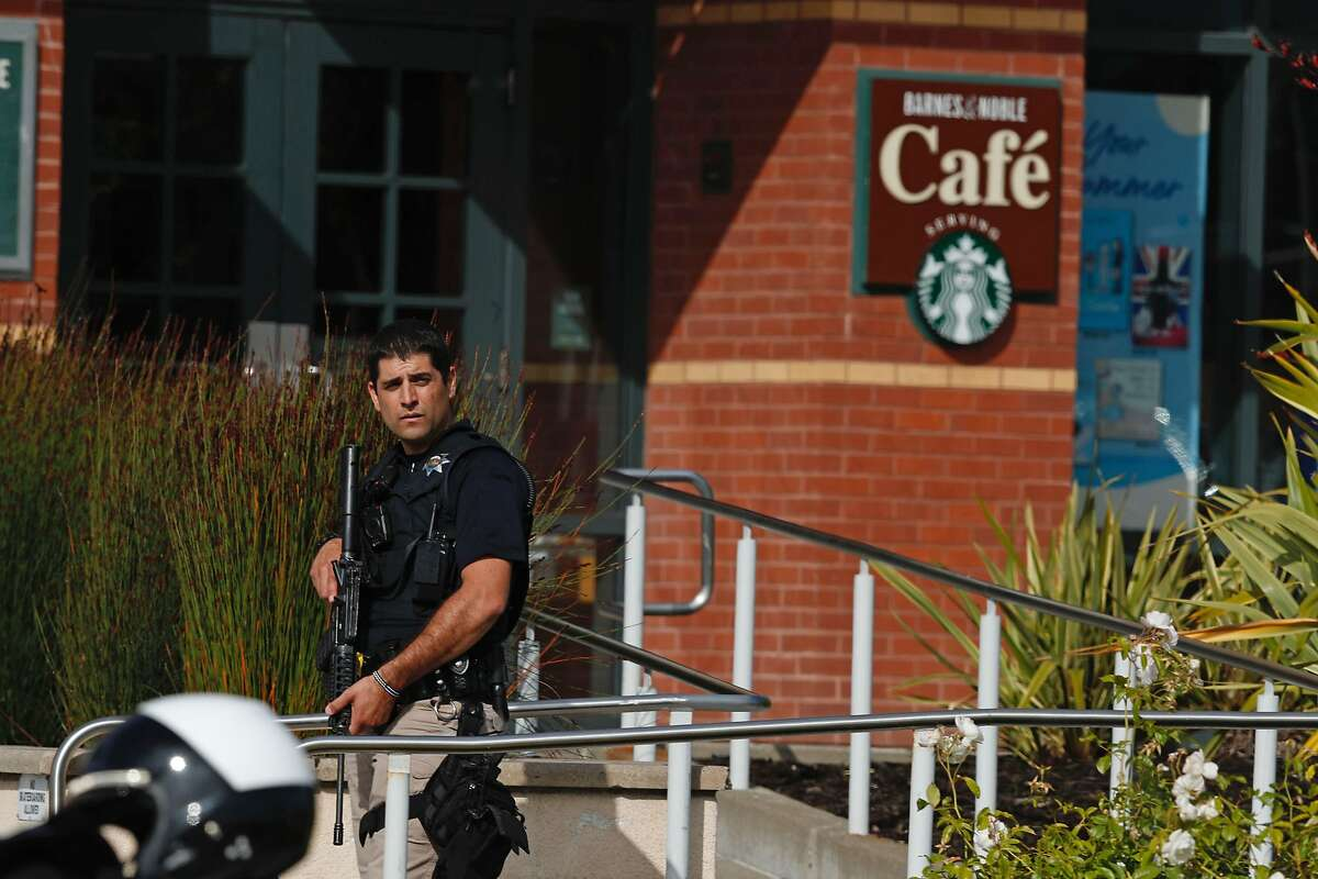 police officer stands in front of the Barnes and Noble at Tanforan shopping center after it was shut down following the shooting of several people on Tuesday afternoon July 2, 2019 in San Bruno, California.