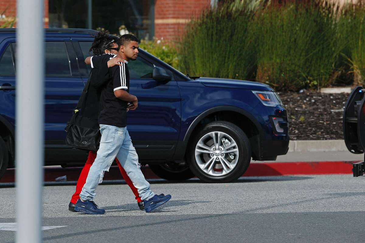 Marcelino Valiente walks with his mother Valerie Ortiz away from Tanforan hopping mall after a shooting on Tuesday afternoon, July 2, 2019, in San Bruno, California. Marcellino was in the theater at the time of the shooting