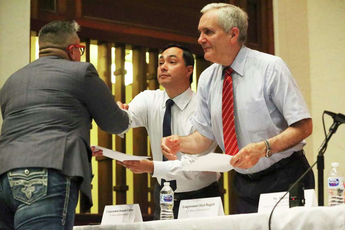 Congressmen Joaquin Castro, center, and Lloyd Doggett receive a copy of a new state law regarding domestic violence from Bexar County Court Judge Rosie Gonzalez during a town hall meeting addressing domestic violence in San Antonio on July 2, 2019.