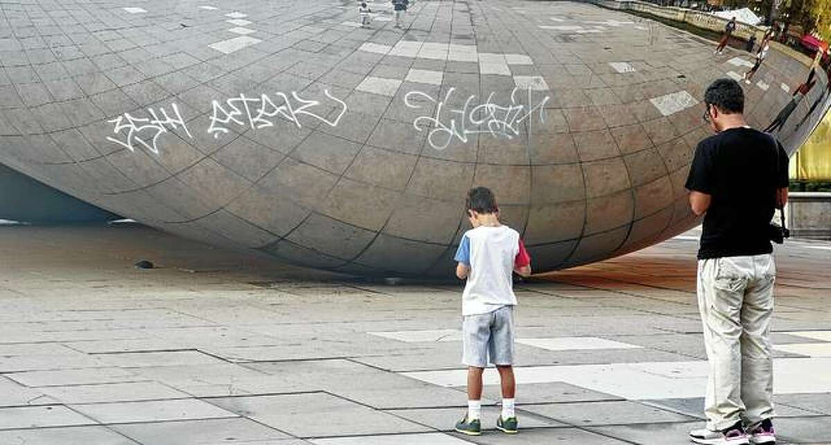 """Graffiti mars the popular giant metallic sculpture known as """"The Bean"""" on Tuesday in Chicago. Seven people suspected of spray-painting graffiti on The Bean and a second downtown Chicago landmark were arrested. Mayor Lori Lightfoot said it was unacceptable that anyone would want to deface the iconic sculpture and memorial walls in a cancer survivors' garden."""