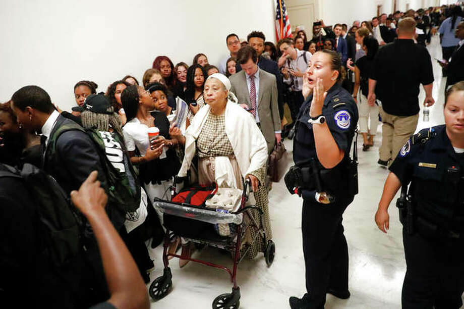A Capitol Police officer speaks to the crowd in the hallway waiting to get into hearing about reparation for the descendants of slaves at the House Judiciary Subcommittee on the Constitution, Civil Rights and Civil Liberties at the Capitol on June 19. Pablo Martinez Monsivais | AP