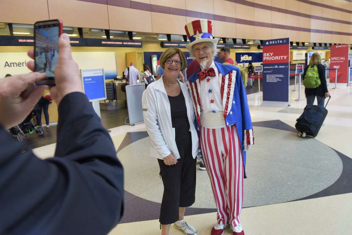 Fred Polnisch portrays Uncle Sam as he poses for a photo with traveler Helen Endres at the Albany International Airport on Wednesday, July 3, 2019, in Colonie, N.Y. Polnisch strolled through the airport greeting travelers on the day before the Fourth of July holiday. (Paul Buckowski/Times Union)