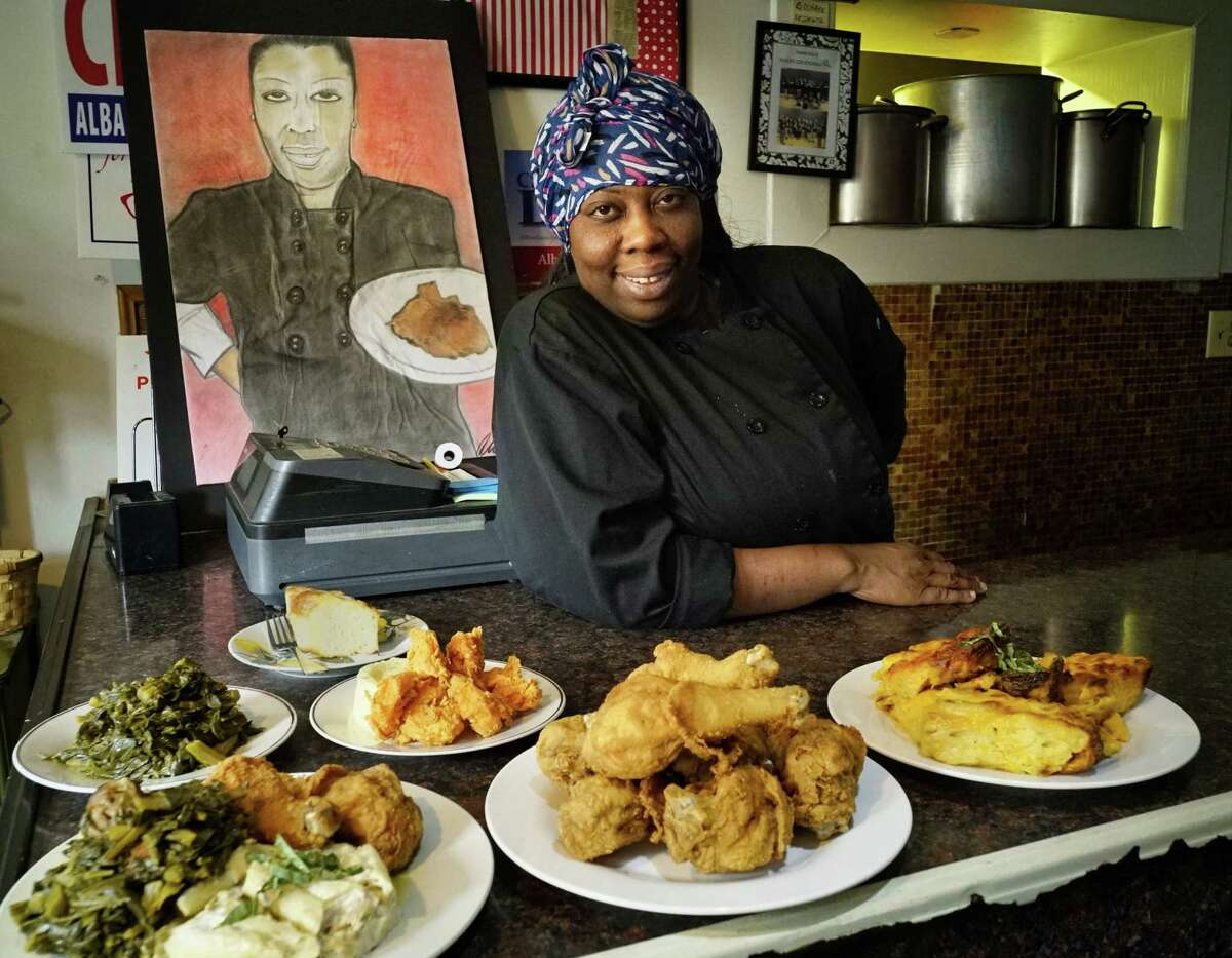 Kizzy Williams, owner of Allie BOs Cozy Kitchen, poses with some of her food on Tuesday, June 11, 2019, in Albany, N.Y. The painting in the background is a portrait of Williams done by the local artist Ali. (Paul Buckowski/Times Union)