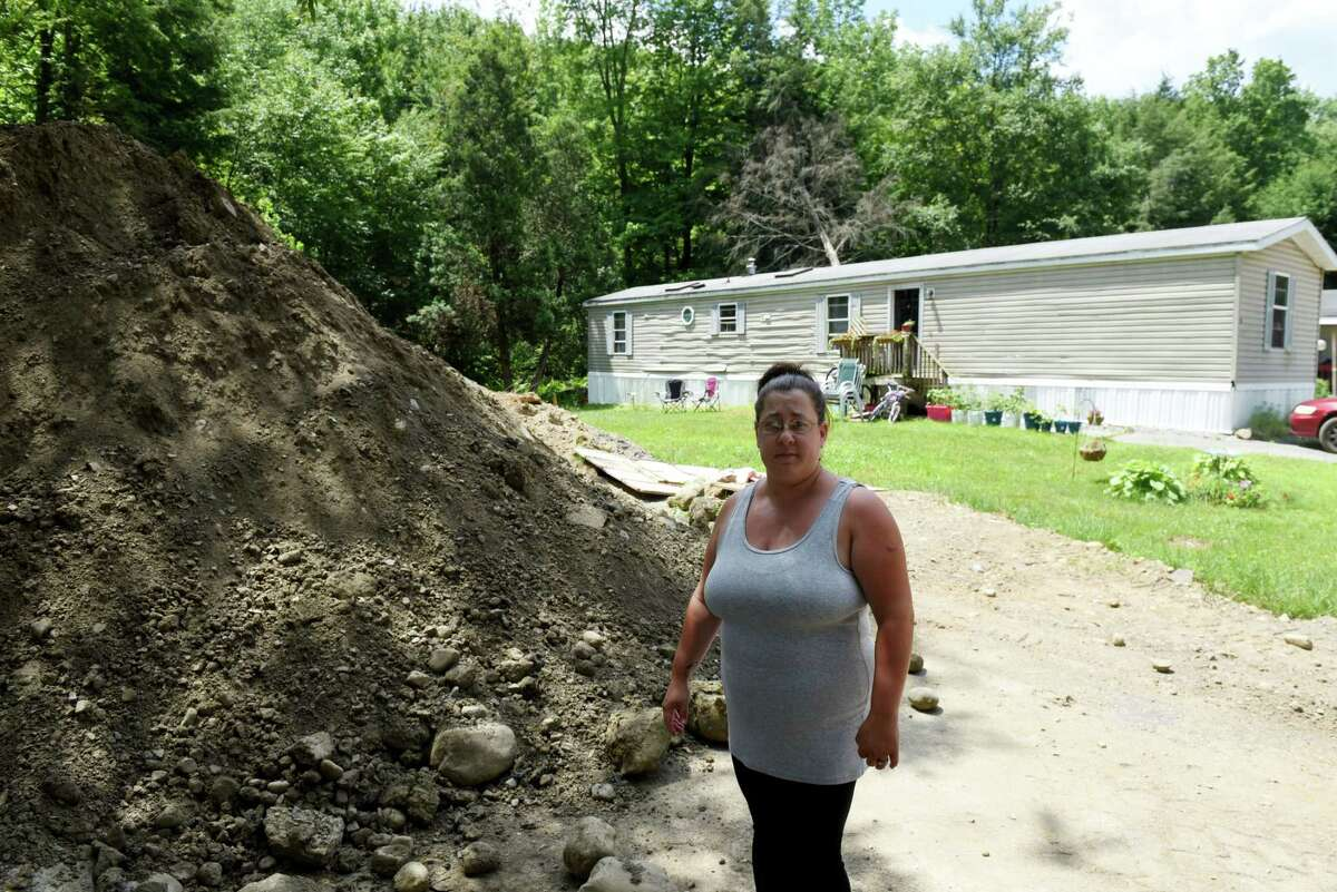Amanda Tanzer, a resident in the Kayadeross Acres mobile home park, is upset with pace of construction progress, and mounds of earth left next to her home on Wednesday, July 3, 2019, in Ballston Spa, N.Y. The facility got $4 million to make improvements in 2016. Work began this year to update its water and sewer system. (Will Waldron/Times Union)