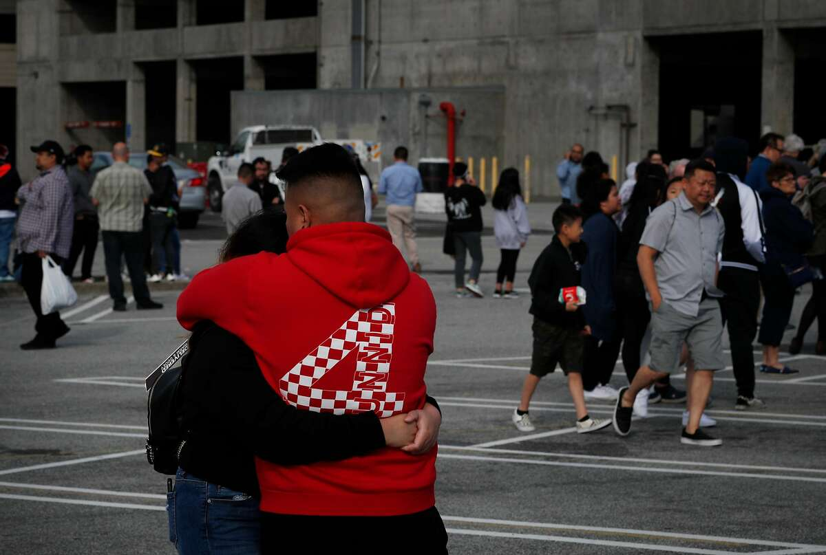A couple who wished to not be indentified embrace as they wait to get back to their car in the Century Theater parking lot at Tanforan shopping mall after a gunman opened fire in the mall in San Bruno, Calif., on Tuesday, July 2, 2019. Two juveniles were wounded by gunfire during the incident.
