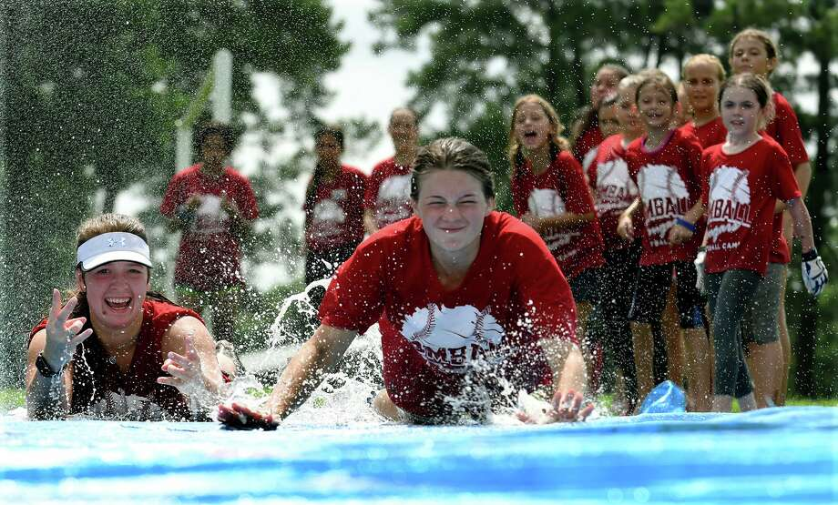 Campers show of their sliding skills during the 2019 Tomball Cougar Softball Camp at THS on June 27, 2019. Photo: Jerry Baker, Houston Chronicle / Contributor / Houston Chronicle