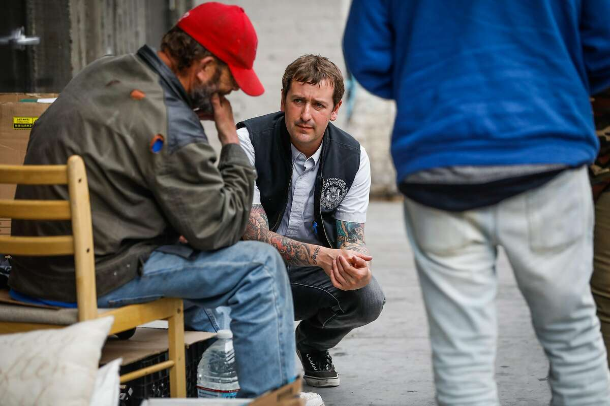 Mark Mazza (center) with the Homeless Outreach Team speaks with a homeless man while doing outreach in the Tenderloin in San Francisco, California, on Wednesday, June 26, 2019.