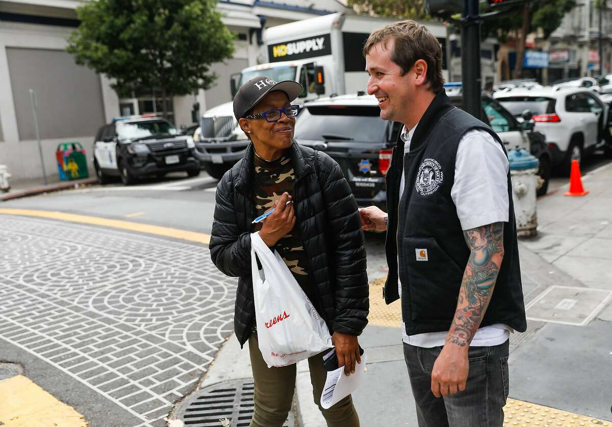Homeless Outreach Team members Deondra Trumbo and Mark Mazza (right) share a laugh as they wait to cross the street and begin their homeless outreach in the Tenderloin in San Francisco, California, on Wednesday, June 26, 2019.