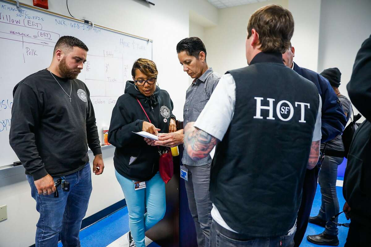 Carolyn Akbar (center, left) looks at paperwork with Brenda Meskan (center,right) during a Homeless Outreach Team meeting ahead of going out on the streets in the Tenderloin in San Francisco, California, on Wednesday, June 26, 2019.
