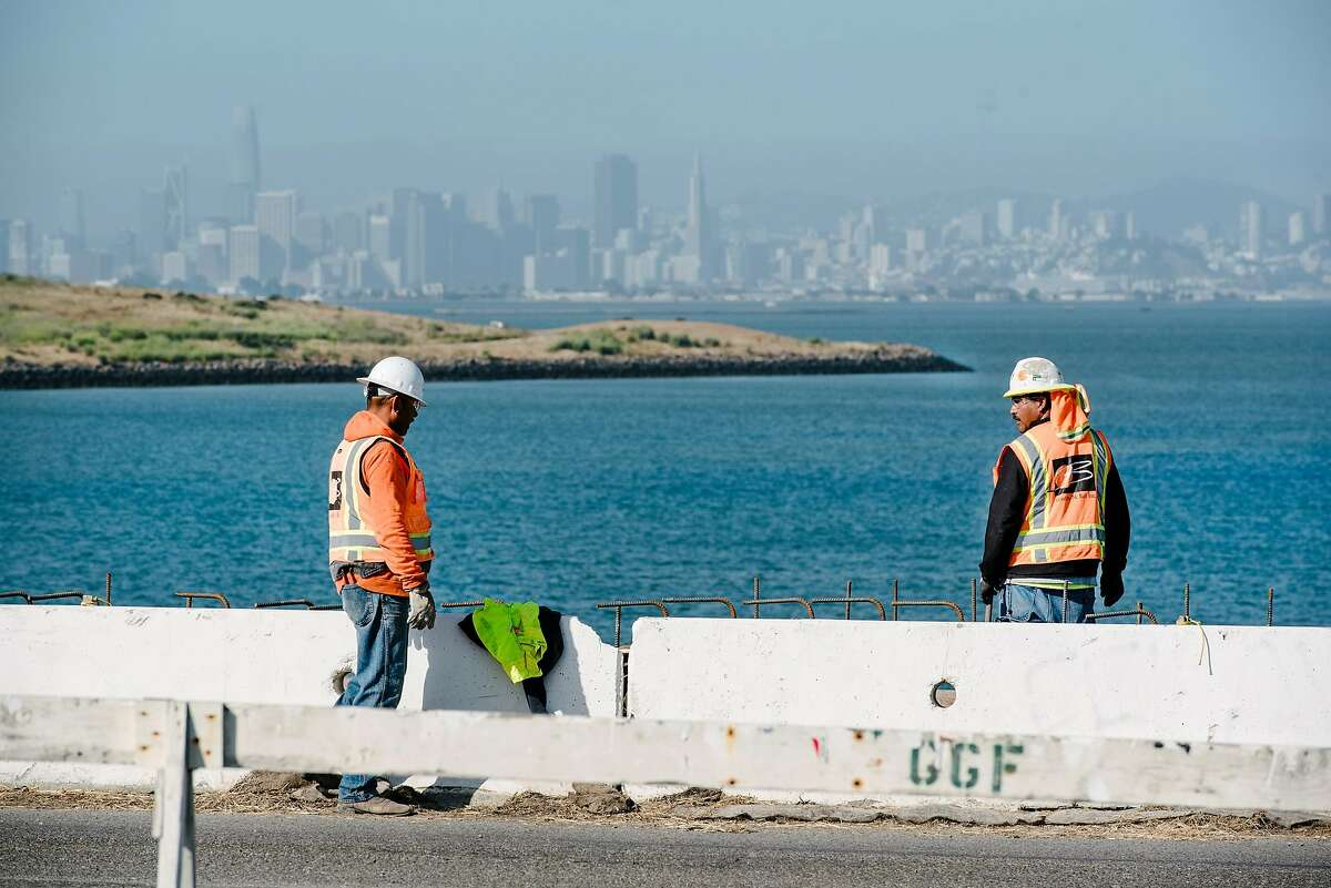 San Francisco is seen in the distance as workers with contractor Gordon N. Ball Inc. work on a section of the Bay Trail near Golden Gate Fields race track in Albany, Calif., on July 3rd, 2019.