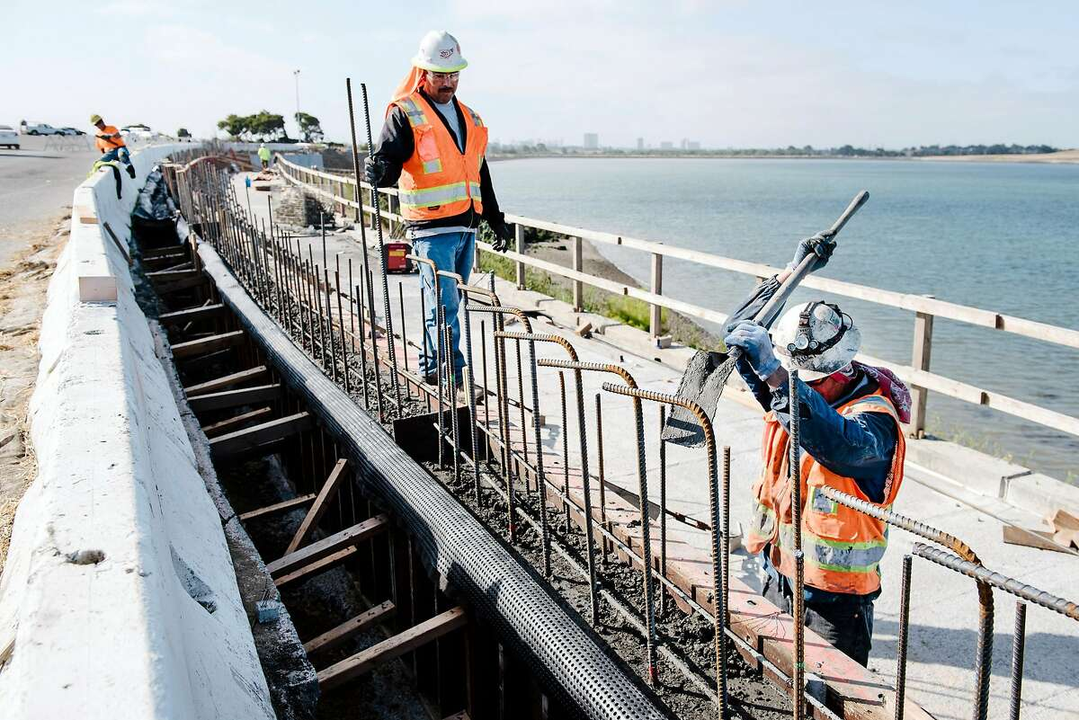 Workers with contractor Gordon N. Ball Inc. work on a section of the Bay Trail near Golden Gate Fields race track in Albany, Calif., on July 3rd, 2019.