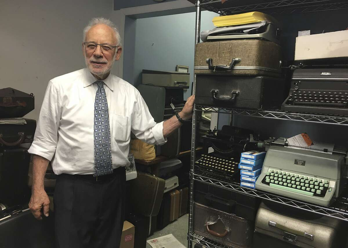 This June 28, 2019 photo shows Paul Schweitzer standing in the Gramercy Typewriter Co. repair shop in New York, alongside a shelf of vintage typewriters. Schweitzer who, with his son, owns the Gramercy Typewriter Co, founded by Schweitzer's father in 1932. Vintage typewriters are sent for repair and restoration daily from around the country, Schweitzer says. (Katherine Roth via AP)
