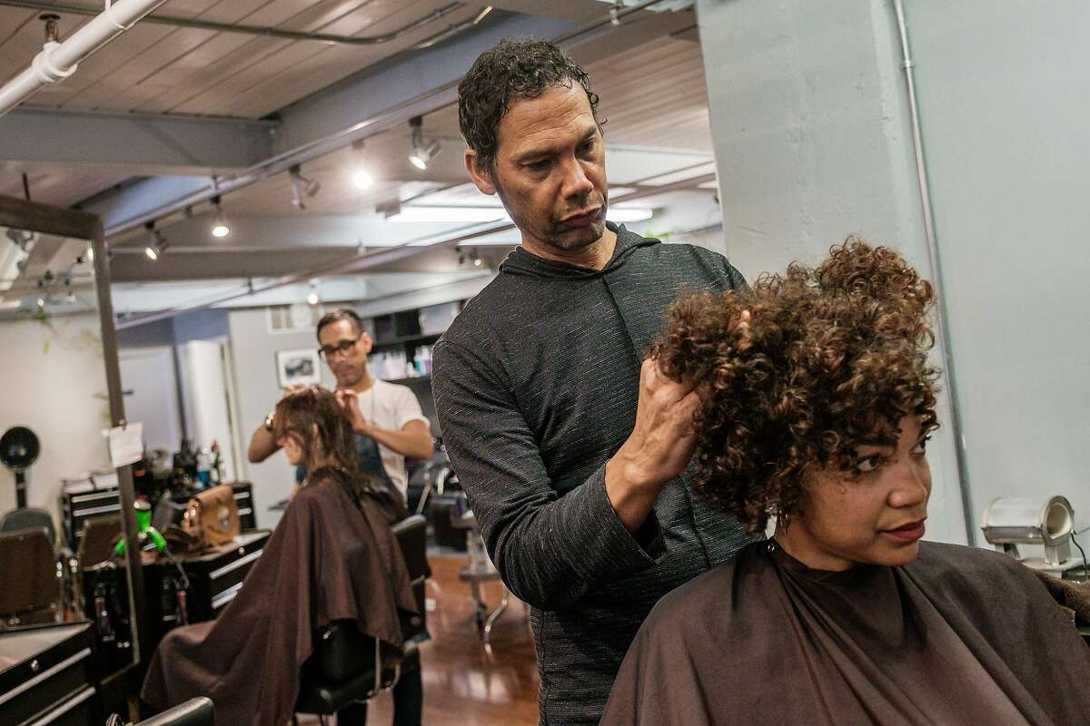 Hair stylist Fritz Clay works on Sherri McMullen's hair at the Hair Play Salon in San Francisco. Gov. Gavin Newsom signed a bill today that would make California the first state to prohibit discrimination against black employees and students who wear natural hair styles.