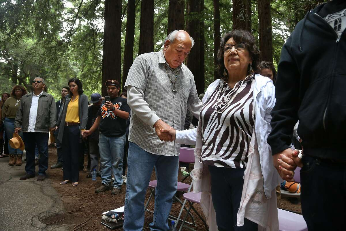 Valentin Lopez, Chair of the Amah Mutsun Tribal Band, center, and tribal bandmember, Clora Hanley, right, and others pray prior to the removal of the El Camino Real bell marker on Friday, 6/21, 2019 at UC Santa Cruz in Santa Cruz, California. The bell marker, which memorializes the California Missions and an imagined route of travel that once connected them, is viewed by the Amah Mutsun and many other California indigenous people as a racist symbol that glorifies the domination and dehumanization of their ancestors. It is being removed at the request of the Amah Mutsun, with support from UCSC faculty members, students, and administrators.