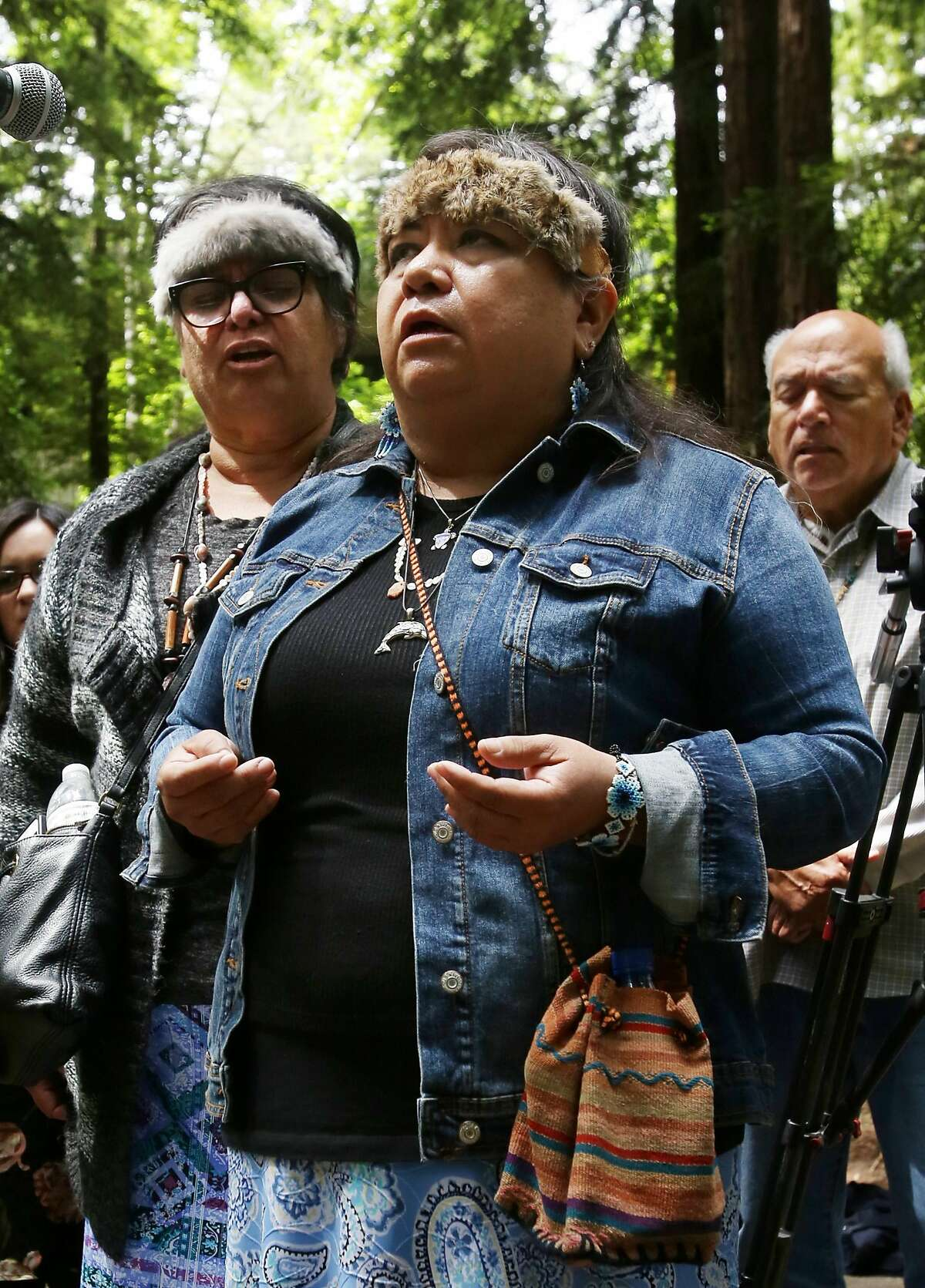Representatives of the Amah Mutsun Tribal Band sing during the removal of the El Camino Real bell marker on Friday, 6/21, 2019 at UC Santa Cruz in Santa Cruz, California. From left are: Lorraine Luna, Catherine Luna and Valentin Lopez. The bell marker, which memorializes the California Missions and an imagined route of travel that once connected them, is viewed by the Amah Mutsun and many other California indigenous people as a racist symbol that glorifies the domination and dehumanization of their ancestors. It is being removed at the request of the Amah Mutsun, with support from UCSC faculty members, students, and administrators.