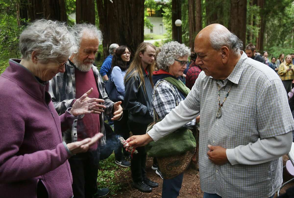 Valentin Lopez, Chair of the Amah Mutsun Tribal Band, right, blesses attendees with burning sage as members of the UC Santa Cruz administration and interested community members witness the removal of the El Camino Real bell marker on Friday, 6/21, 2019 at UC Santa Cruz in Santa Cruz, California. The bell marker, which memorializes the California Missions and an imagined route of travel that once connected them, is viewed by the Amah Mutsun and many other California indigenous people as a racist symbol that glorifies the domination and dehumanization of their ancestors. It is being removed at the request of the Amah Mutsun, with support from UCSC faculty members, students, and administrators.