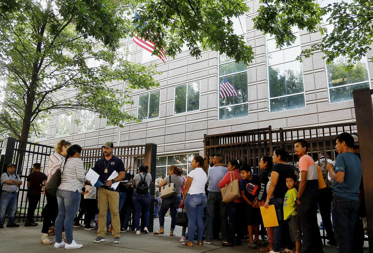 HFM TBA**An Immigration and Customs Enforcement official assists people waiting to enter the building that houses ICE and the Atlanta Immigration Court, Wednesday, June 12, 2019, in Atlanta. (AP Photo/Andrea Smith)