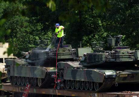 A worker uses pressure washer to clean an Abrams tanks on a flat car in a rail yard, Tuesday, July 2, 2019, in Washington, ahead of a Fourth of July celebration that President Donald Trump says will include military hardware.