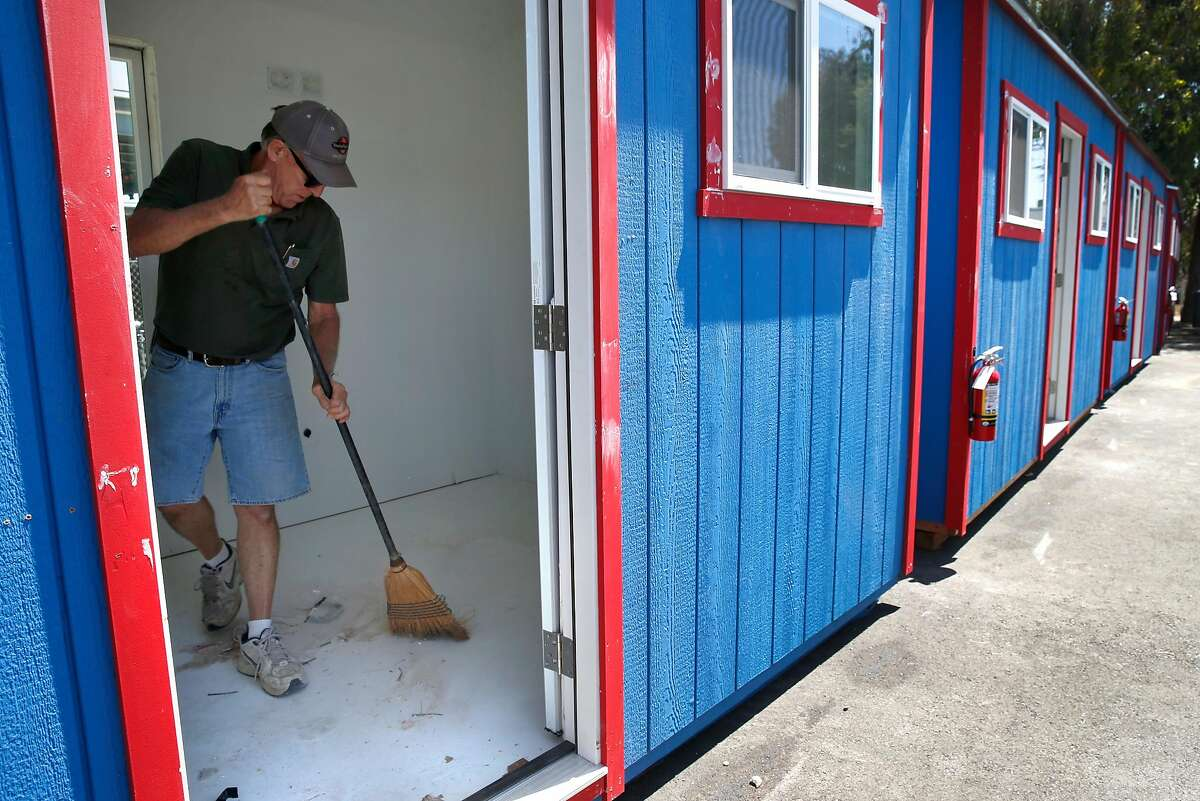 Bill Kelley, of California Sheds, prepares a home in a new community of portable sheds for homeless residents below the MacMarthur Maze in Oakland, Calif. on Wednesday, July 3, 2019. The first of the 80 or so residents are scheduled to move into the tiny homes near Wood and 34th streets on Sunday.