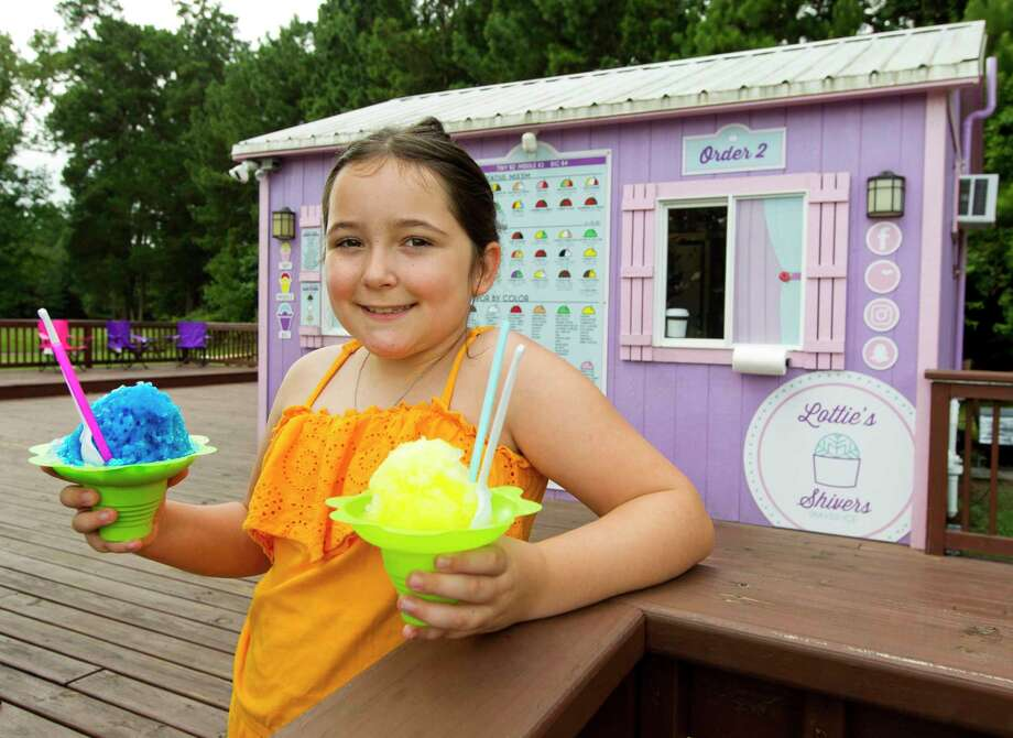Lottie Portales, owner of Lottie Shivers Shaved Ice, poses for a portrait at her snow cone stand on Maurel Drive, Thursday, July 3, 2019, in Conroe. Portales, 9, started her business with a Snoopy snow cone machine and one flavor in pre-kindergarten, now she works out of a purple stand, has purchased several shavers and customers can enjoy a mix of 177 different flavors. Photo: Jason Fochtman, Houston Chronicle / Staff Photographer / Houston Chronicle