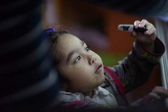 Abcde Rodriguez, 6, writes on a board under the watchful eye of special education teacher Veronica De Los Santos at Green Academy on Sept. 25, 2018.