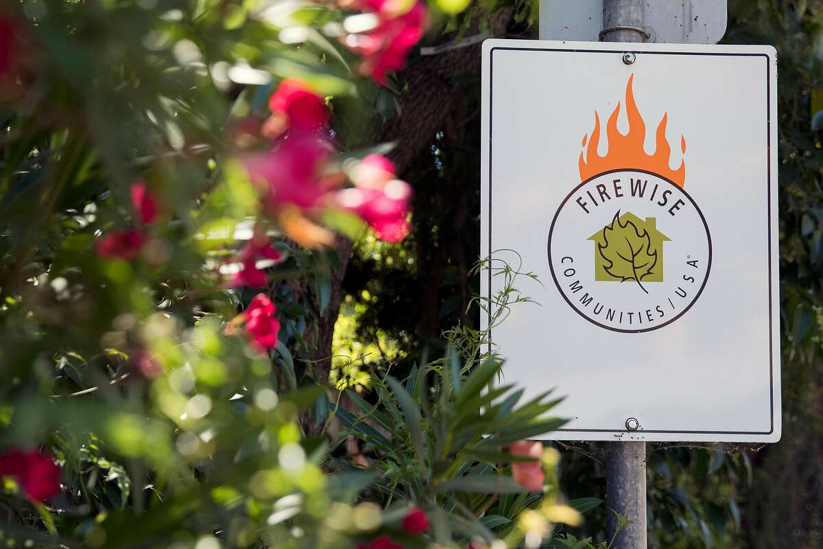 A sign along East Dunne Avenue marks the participation of the Jackson Oaks neighborhood in the FireWise program in Morgan Hill, Calif. Wednesday, July 3, 2019.
