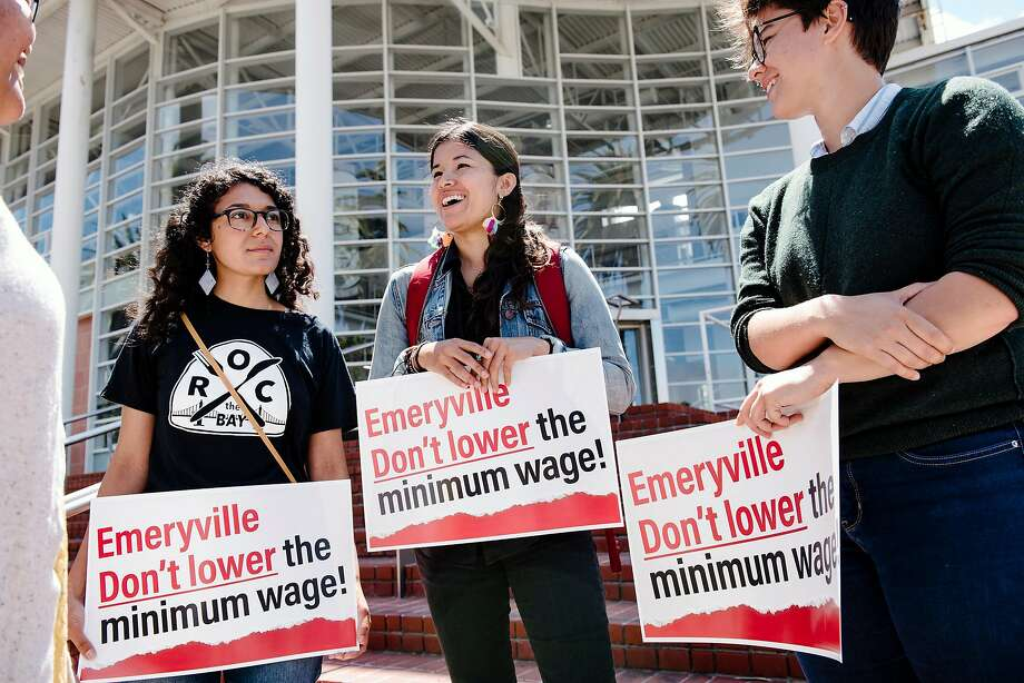 Maricela Gutierrez, left, Maria Moreno, and Hanna Batlan, with the group R.O.C., Restaurant Opportunities Center United, hold signs while joining members of the Service Employees International Union 1021 and other labor activists gather outside City Hall to oppose new wage legislation recently passed by the city council, in Emeryville, CA on June 26th, 2019. The Emeryville City Council in a 3-2 vote passed an ordinance that would create a lower minimum wage for workers at restaurants with 20 or fewer locations globally. Photo: Michael Short / Special To The Chronicle