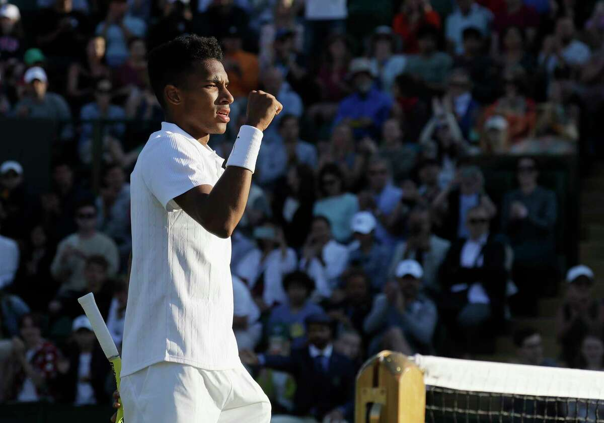 Canada's Felix Auger-Aliassime celebrates after beating Corentin Moutet of France in a Men's singles match during day three of the Wimbledon Tennis Championships in London, Wednesday, July 3, 2019. (AP Photo/Kirsty Wigglesworth)