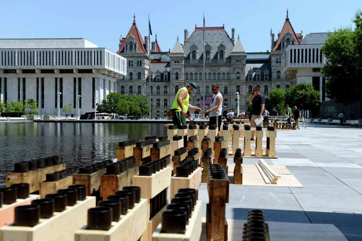 Members of the pyro crew of Santore's World Famous Fireworks move racks for firework shells in preparation for the 43rd annual Independence Day fireworks show at Empire State Plaza on Wednesday, July 3, 2019, in Albany, N.Y. There will be approximately 10,000 fireworks shells fired during the celebration. (Catherine Rafferty/Times Union)