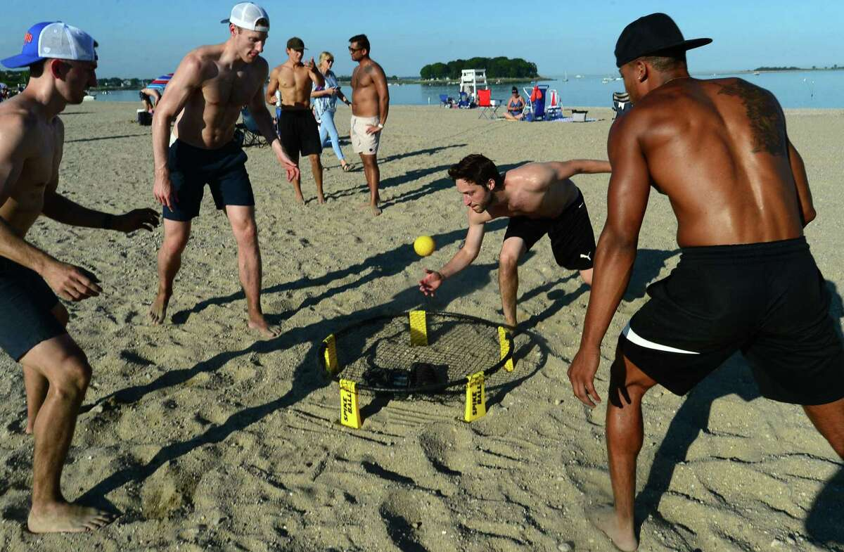 Norwalk residents David Hendreson, Jeff Powers, James Lucchesi, and Marc Miller play a beach game as lLocals gather for the annual fireworks show at Calf Pasture Beach on Wednesday, July 3, 2019, in Norwalk, Conn. In a briefing at Hammonassett Beach State Park in Madison on Friday, state officials struck a positive note about Connecticut's response to the pandemic but also advised residents to continue to take precautions this weekend. Governor Ned Lamont told folks to enjoy the holiday weekend - but to do so