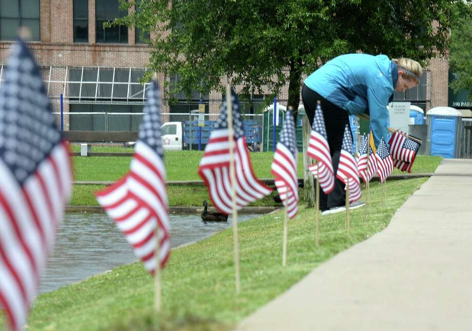 Rachel Parker installs flags around the lake at Beaumont's Event Center on Wednesday in preparation for the city's Fourth of July celebration on Thursday. The event will host music, food and drinks with a fireworks display at 9 pm. Gates open at 5. Photo taken Wednesday, 7/3/19 Photo: Guiseppe Barranco/The Enterprise, Photo Editor / Guiseppe Barranco ©