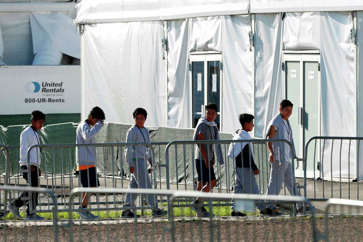 FILE - In this Feb.19, 2019 file photo, children line up to enter a tent at the Homestead Temporary Shelter for Unaccompanied Children in Homestead, Fla. A government spokesman says President Donald Trump?s administration is evaluating vacant properties near five U.S. cities as potential permanent sites to hold unaccompanied migrant children. Department of Health and Human Services spokesman Mark Weber said Wednesday that property is being assessed in and around Atlanta; Phoenix; Dallas; Houston; and San Antonio, Texas. (AP Photo/Wilfredo Lee, File)
