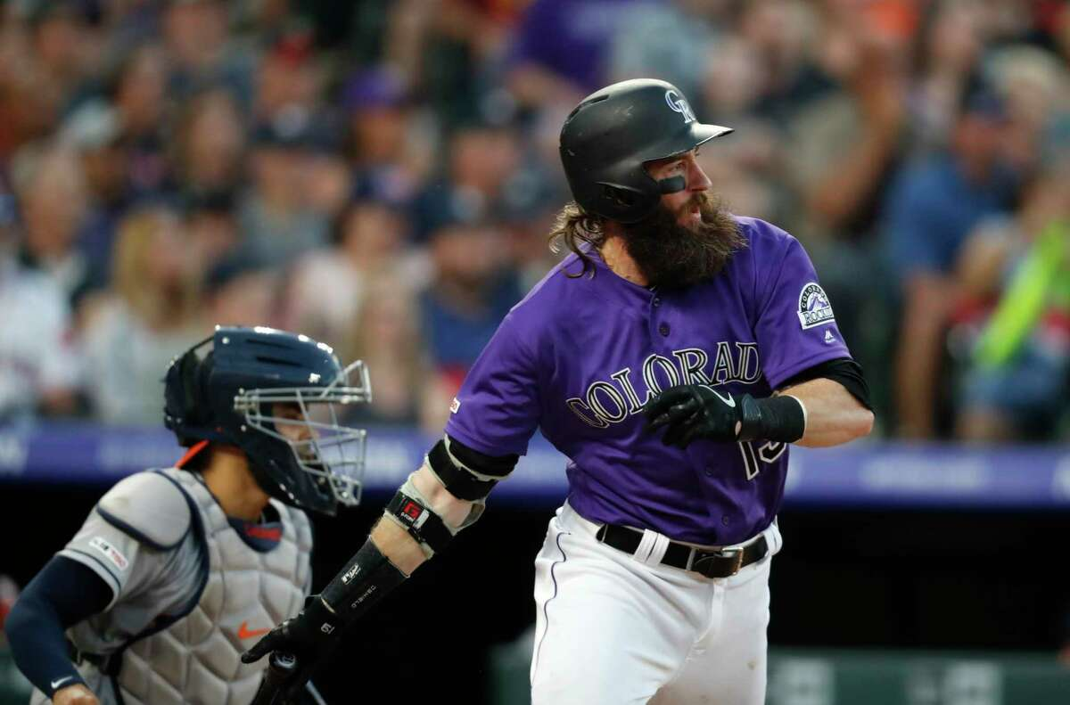 Colorado Rockies' Charlie Blackmon watches his RBI single off Houston Astros relief pitcher Chris Devenski, next to catcher Robinson Chirinos during the seventh inning of a baseball game Wednesday, July 3, 2019, in Denver. (AP Photo/David Zalubowski)