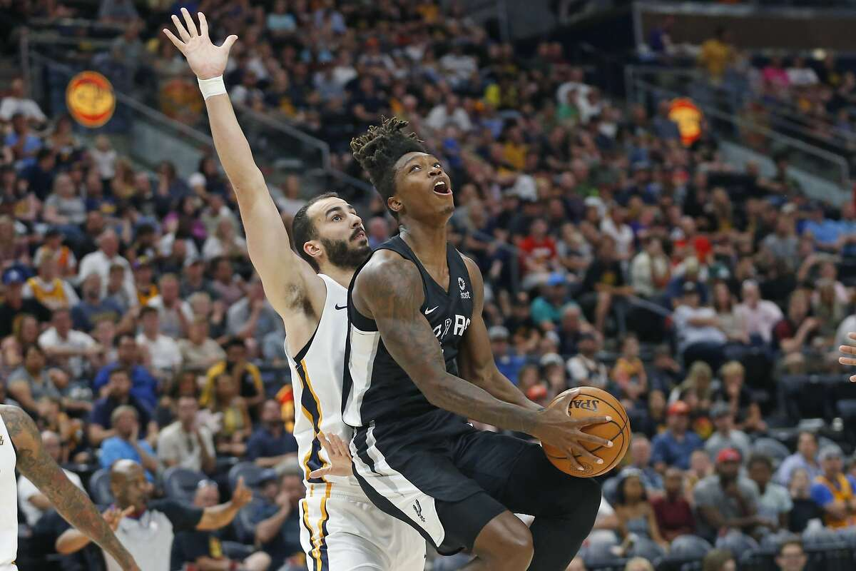 San Antonio Spurs guard Lonnie Walker IV, right, lays the ball up as Utah Jazz center Josh Sharma defends during the first half of an NBA summer league basketball game Wednesday, July 3, 2019, in Salt Lake City. (AP Photo/Rick Bowmer)