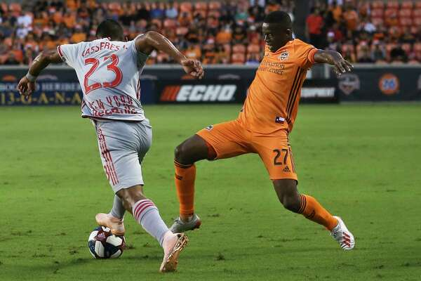 Houston Dynamo midfielder Boniek Garcia (27) and New York Red Bulls midfielder Cristian Casseres Jr (23) battle for the ball during the first half of the MLS game at BBVA Stadium on Wednesday, July 3, 2019, in Houston.