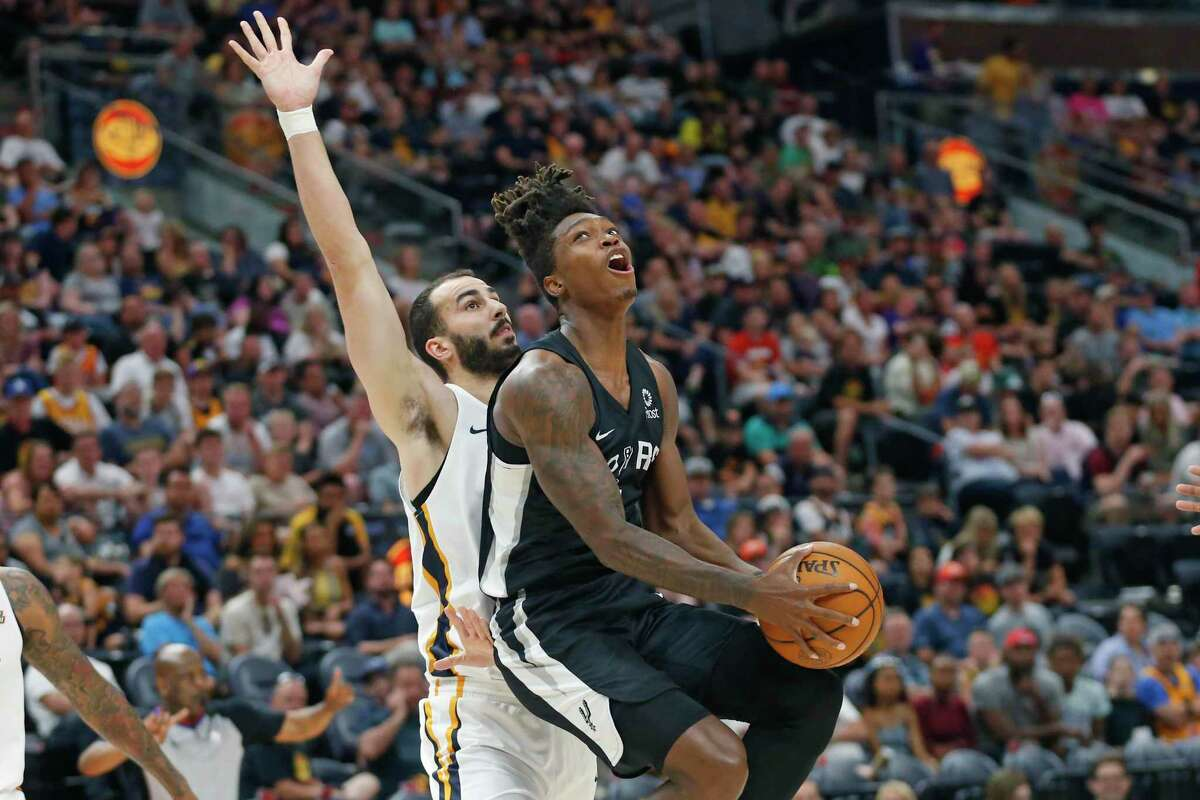Spurs guard Lonnie Walker IV, right, lays in the ball as Jazz center Josh Sharma defends during the first half Wednesday. Walker finished with a game-high 19 points.