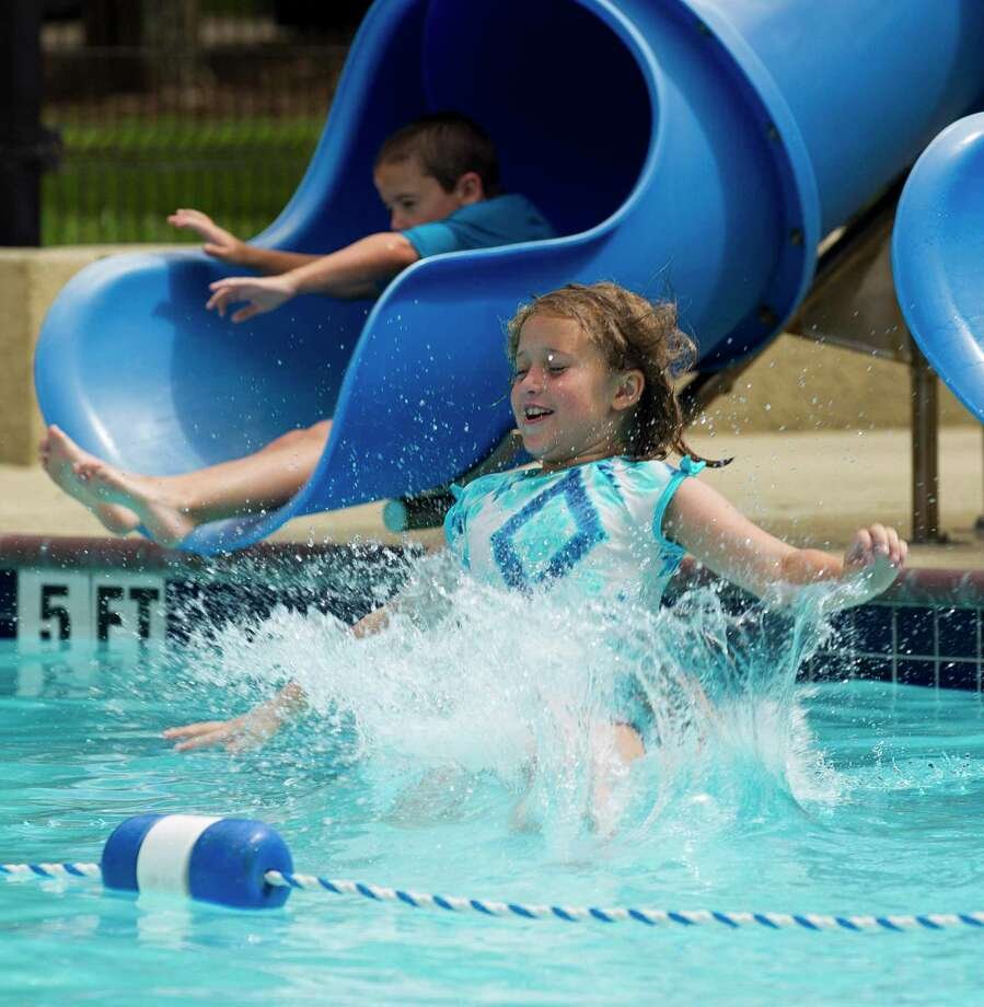 Rachel Allen slides into the water at the Alden Bridge subdivision pool, Thursday, July 4, 2019, in The Woodlands. Photo: Jason Fochtman, Houston Chronicle / Staff Photographer / Houston Chronicle