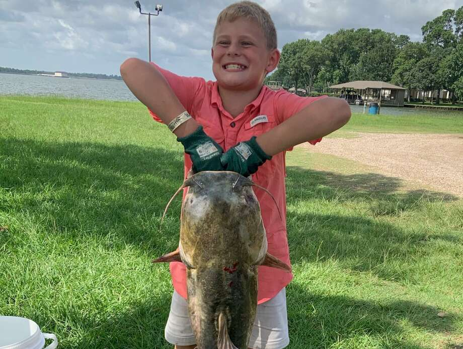Mason Turner, 10, poses with the 28-pound catfish he caught in Lake Conroe on Wednesday, July 3, 2019. Turner, who was fishing from a dock near his family's neighborhood marina, was using bass lure and a 12-pound line. A neighbor helped Turner get the fish - which measured 39 inches long, 22 inches around the body and 20 inches around the head - out of the water with a net. Photo: Submitted