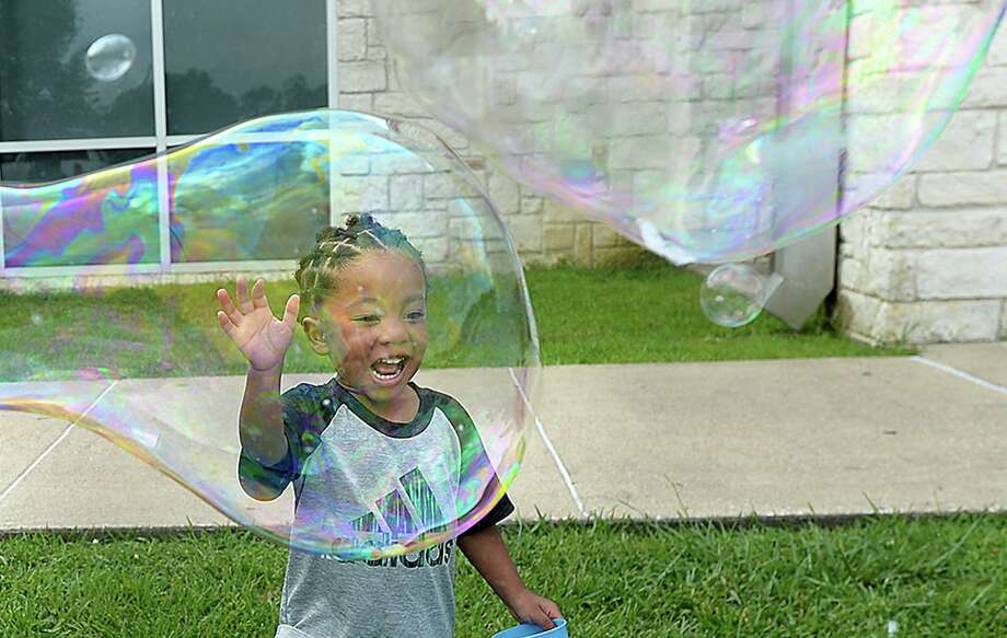 Roman Frank reacts as his mother Asia Perkins creates a large bubble during the Texas Energy Museum and Beaumont Public Library's annual Bubble Day event at the Theodore Johns Library Wednesday. A second event will be held July 10, 11:00 a.m. - 12:30 p.m. at the Rogers Park Community Center. Children and adults can enjoy making large bubbles outdoors, and explore the science of bubbles at various hands-on stations inside.  Photo taken Wednesday, June 26, 2019  Kim Brent/The Enterprise Photo: Kim Brent / Kim Brent/The Enterprise / BEN