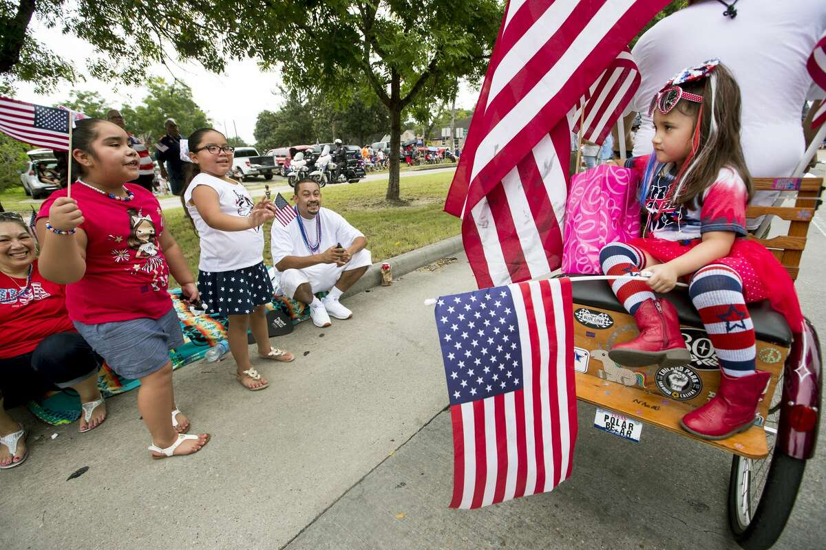 2019: Naomi Mae Sanchez rides on the back of a flag adorned trike as she rides with the E5 Tailgaters in the 20th Annual Lindale Park 4th of July Parade on Thursday, July 4, 2019, in Houston.
